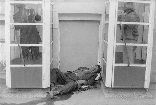 An alcohol-induced person sleeps between two telephone booths