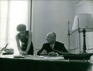 Gaston Defferre looks to a woman writing something on the table, 1969.