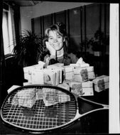 Tennis player Catarina Lindqvist sits with big bundles of money on the table