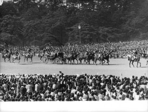 Parade of horses in the middle of the crowd in Tokyo, Japan.