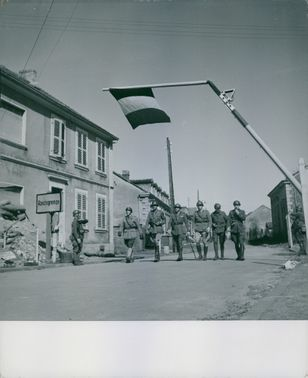 French troops walking on the road.