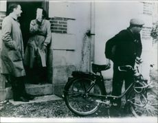 """Man leaving with his cycle, two men looking at him.   """"__ slaying""""  1960"""