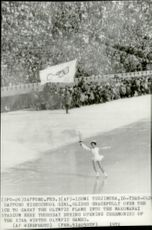 A 16-year-old Japanese artisan carries the torch the last bite to the fire at Makomani Stadium.
