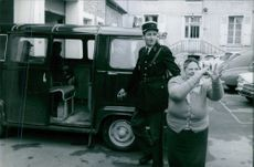 A man and a woman standing beside a vehicle.     1969