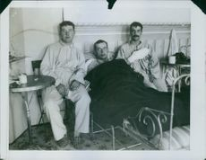 Three British wounded soldiers sitting in the hospital bed.
