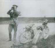 A soldier standing in front of his cycle and looking through a binocular.