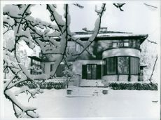 Front side of a big house which is covered by snow.