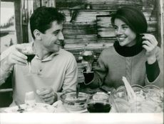 Sacha Distel dining with woman.