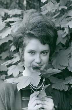 Alice Dona is holding a leaf.
