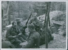 Soldiers sitting, relaxing and smoking together in forest. 1941