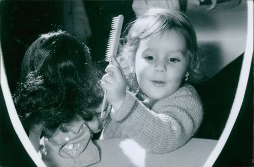 A child combing a wig hair.