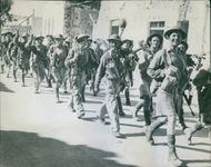 Colonial troops marching together in the street.