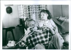 Nick Nolte holding a phone while Whittni Wright trying to get it from her.