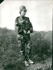 A woman named Yasmina in a military uniform standing and looking away.  Taken - 25 Mar 1964