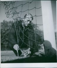 A footballer placing net on the pole, in the ground.
