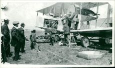 Sightseers watching the vimy aircraft being prepared for the flight from newfoundland piloted by alcock and brown.