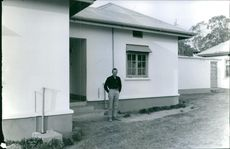 Man standing outside of a house and looking towards the camera.