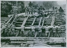 Soldiers pushing the blocks of wood in Burma.