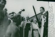 Thor Heyerdahl is kneeling at the traditional ceremony on arrival at Bridgetown