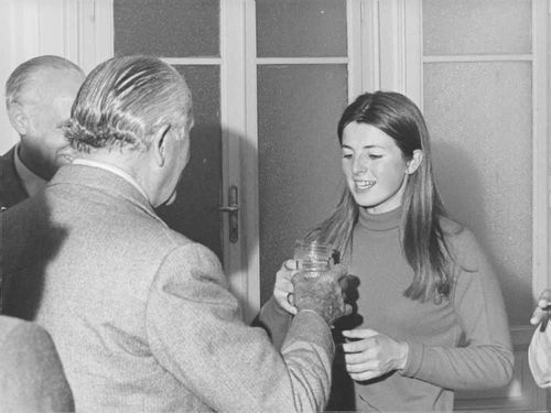 A man toasting drink glass with woman.