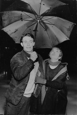 Jacques Charrier holding umbrella and walking in the rain with a woman.