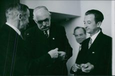 Eddy Velander standing and talking with men.