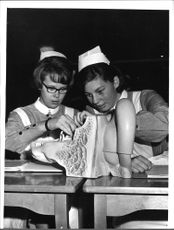 Two nurses from the Red Cross inspects the model of the body part.