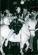 Martine Carol riding a pony at a party.