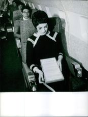 Passengers sitting and relaxing on the plane.