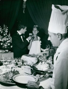 A man and a woman having a toast at the buffet table.