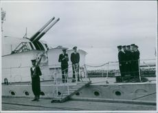 Military officers and sailors on a docked battleship in Norway.
