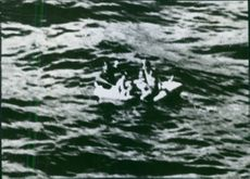 People in boat in sea.