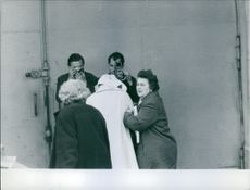 A photo of a covered person being assisted by women pictured by camera men.