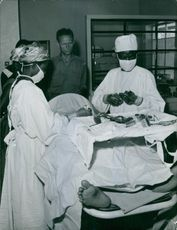 """A patient being treated by a doctor, with a nurse assisting him and other people standing with them and looking at the procedure.  """"Congo""""  1961"""
