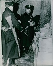 Officers standing outside the house, looking.1946