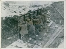 Soldiers building a wooden winter shelter.