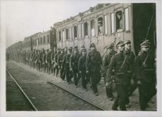 Soldiers moving forward together beside of a train line, 1916.