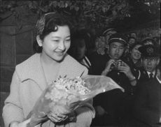 Princess Michiko of Japan smiling to the cameras while holding a flower bouquet.