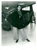 Eartha Kitt on the fly palace wearing black coat