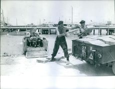 Soldiers loading boxes in a vehicle.