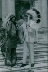 Sargent Shriver wearing Indian tribal headdress while standing beside a Native American Indian.