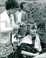 A woman combing Jane Asher's hair while on the set of her film,