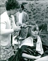 "A woman combing Jane Asher's hair while on the set of her film, ""The Buttercup Chain."""