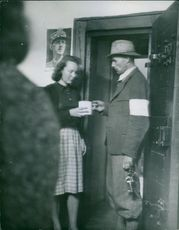 The prisoners receive a plate of thick soup brought to them by a German policeman.