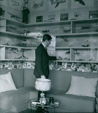A photo of Prince Simeon Borisov Saxe-Coburg-Gotha looking at his airplane collections displayed in the room.