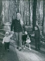 Eliette von Karajan with her two daughters, Isabel and Arabel walking with their pet dog.