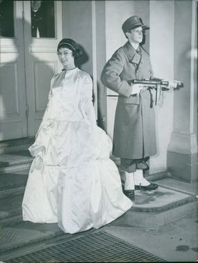 A young woman wearing a gown, smiling and posing for the camera, behind her is a soldier holding his gun and guarding his post.