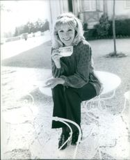 Susan Hampshire sitting while holding a cup on her hand and smiling.