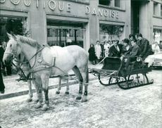Marielle Goitschel sitting with people on horse cart.
