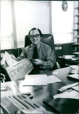 British trade union Olive Jenkins holding a newspaper while sitting behind the desk, 1976.